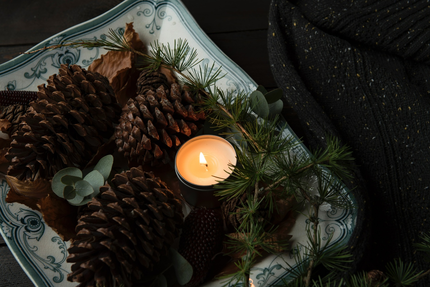lighted candle on plate beside the pinecones - Möbel Preiss