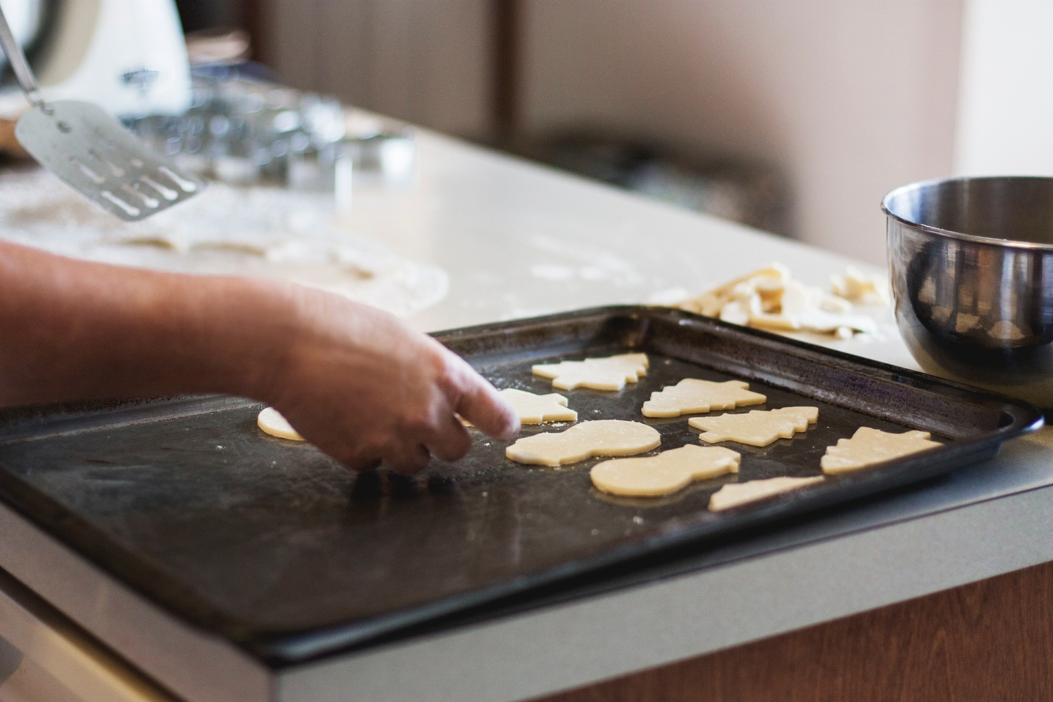 person lining assorted-shaped cookies on baking sheet inside kitchen - Möbel Preiss
