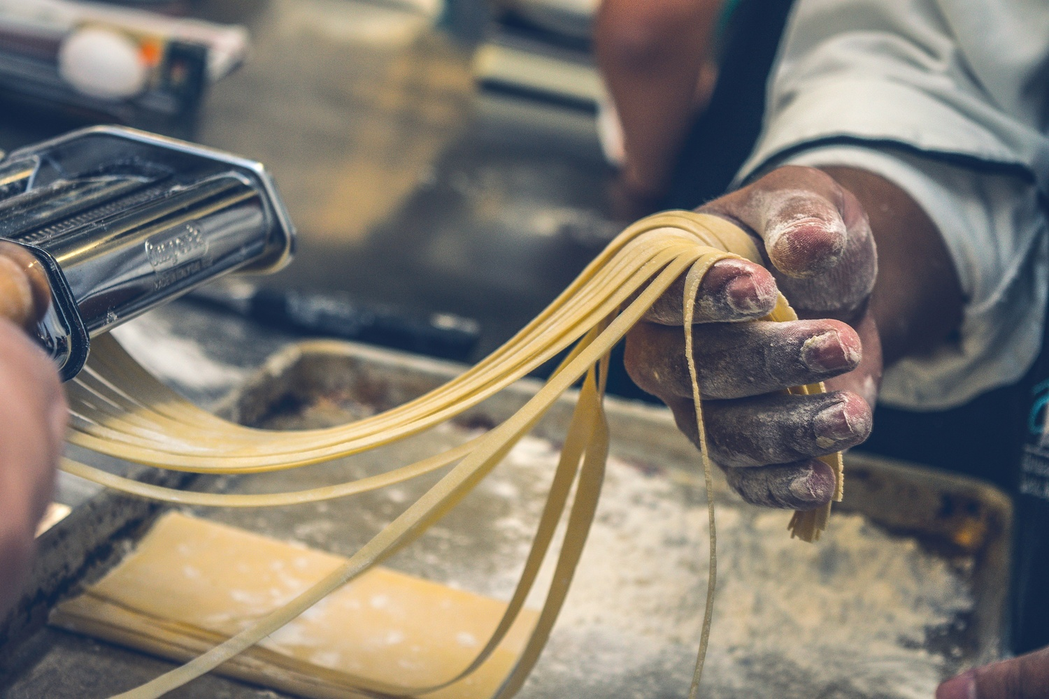A chef holding long strands of pasta coming out of a machine - Möbel Preiss