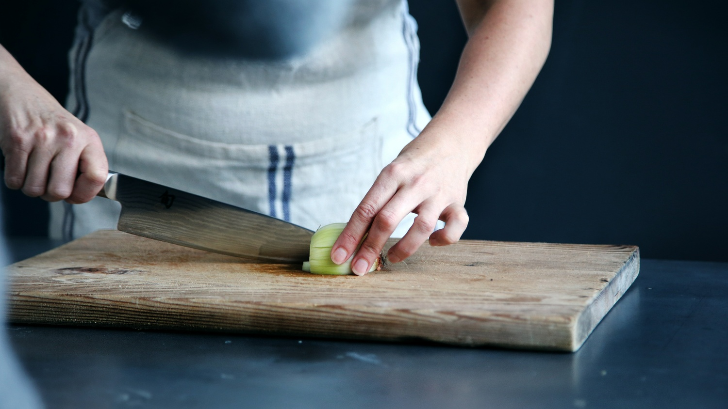 Chef slices an onion on a cutting board - Möbel Preiss