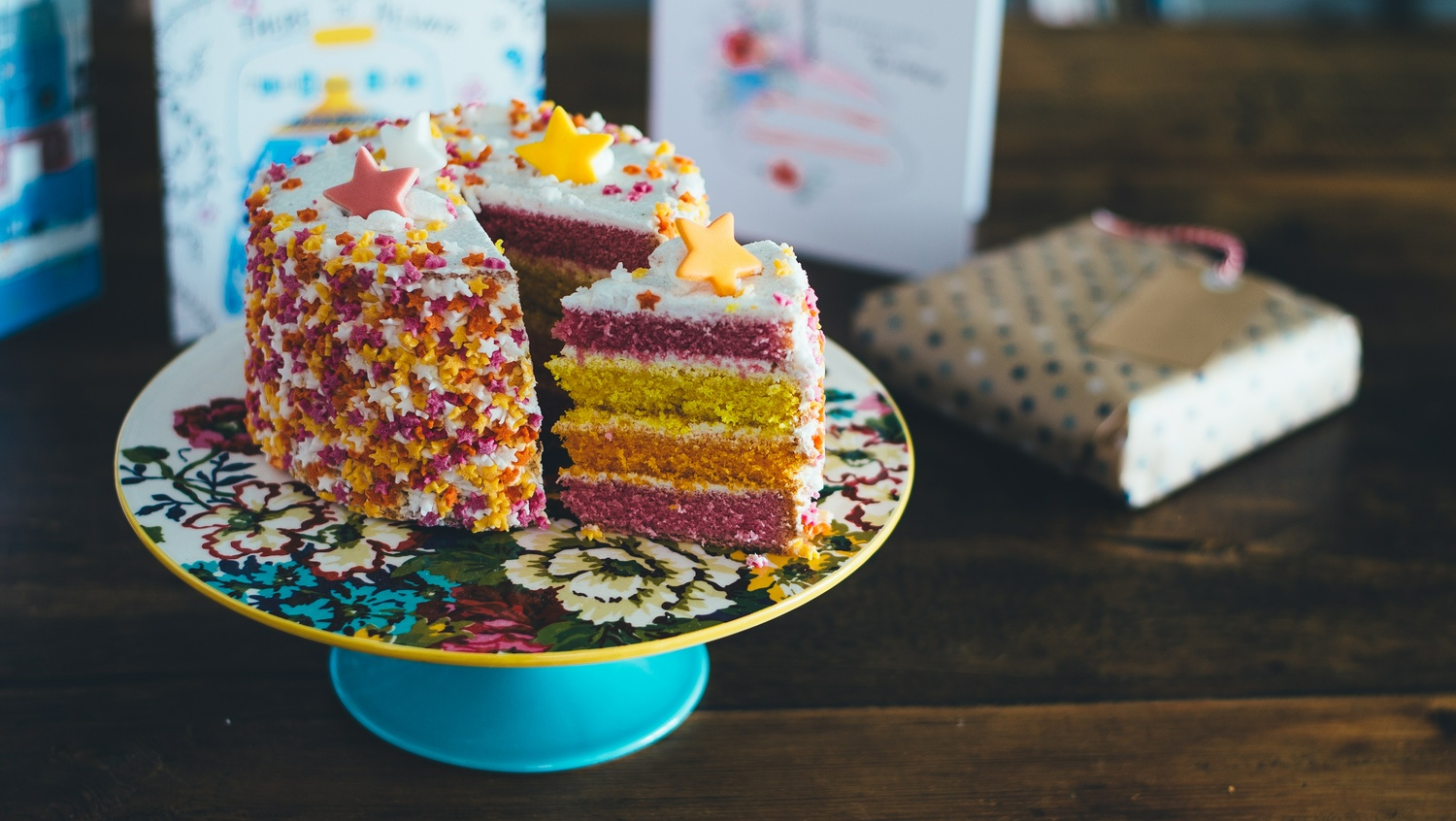 A birthday cake with rainbow sponge and stars on top, with a slice cut out and sat at an angle on the plate - Möbel Preiss